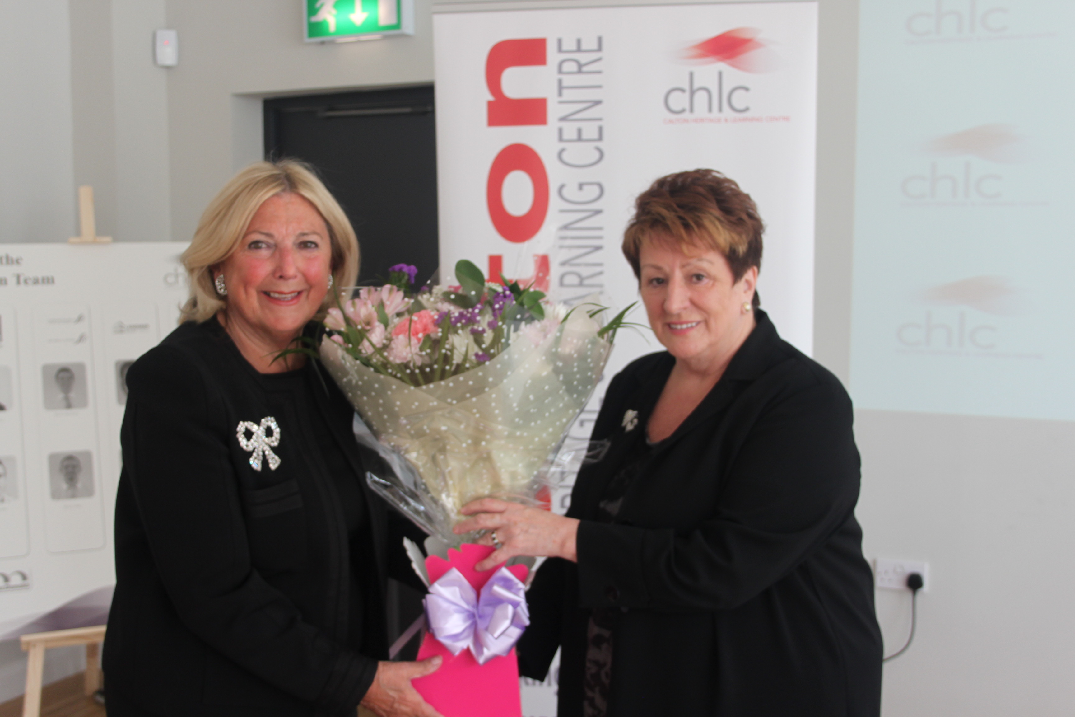 - Betty Cosgrove presents Ruth Simpson with a floral bouquet