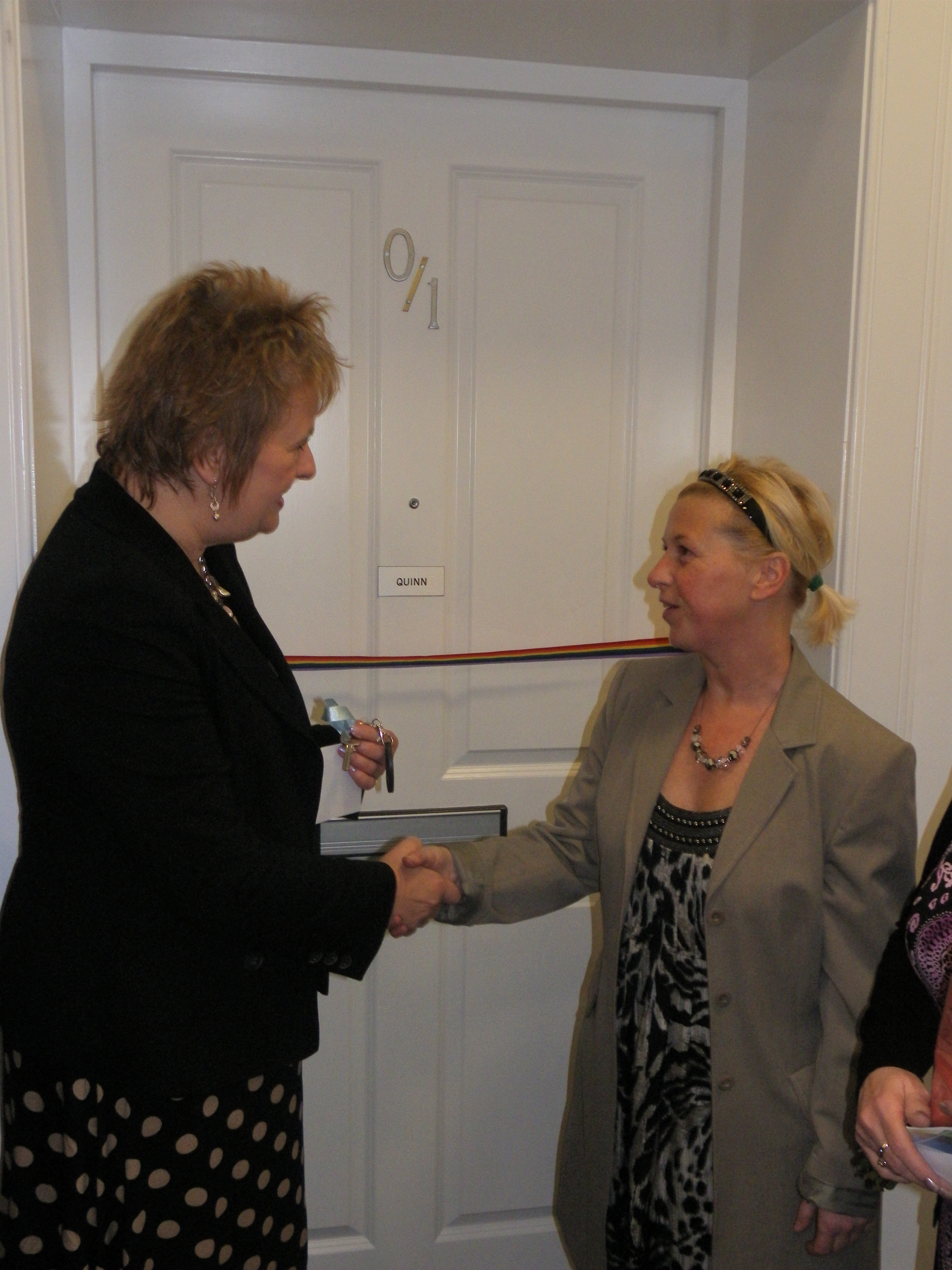 - Roseanna Cunningham MSP cuts ribbon and presents Jacqueline Quinn with the keys to her new home